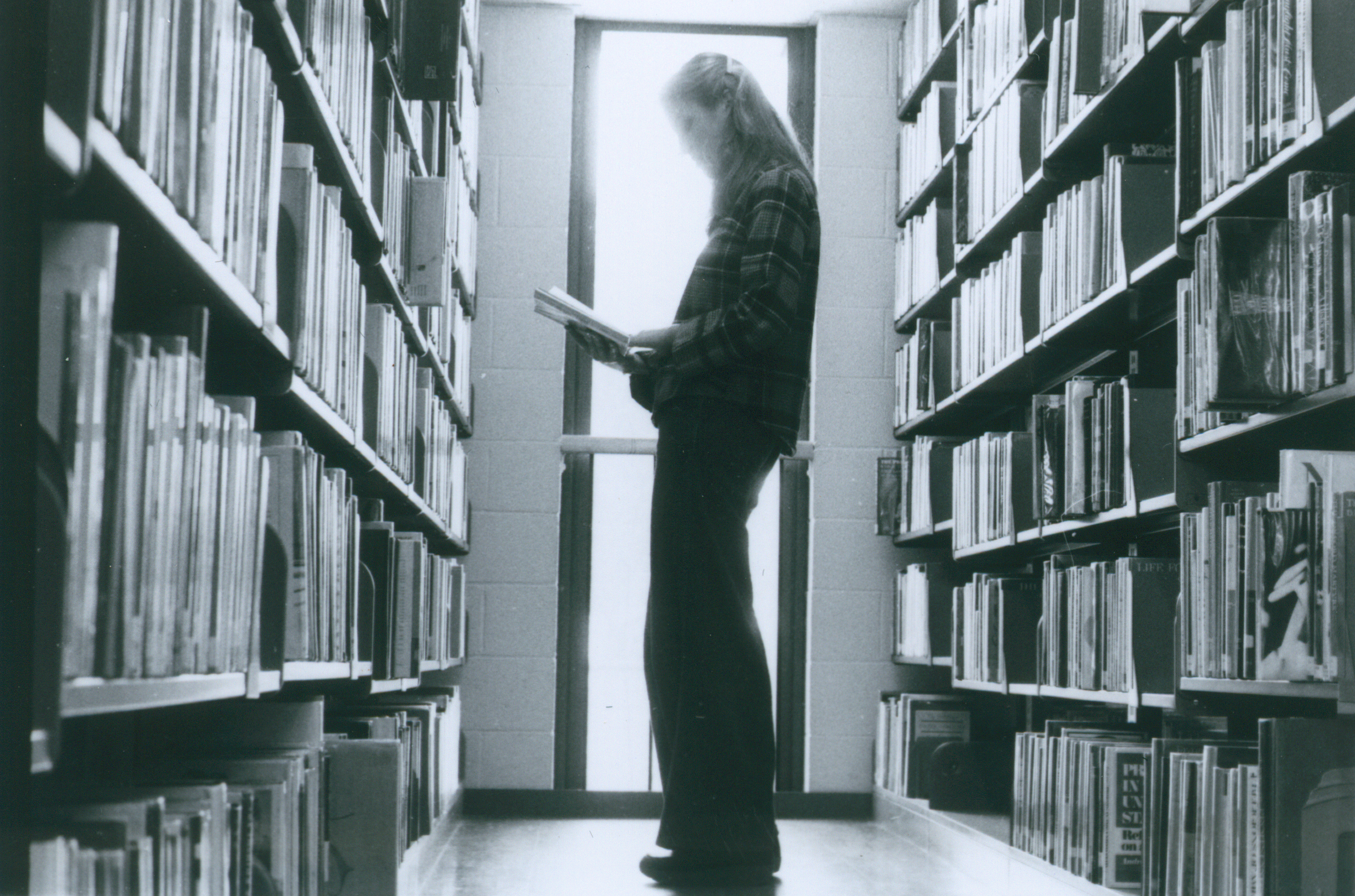 visitor reading in the bookstacks in 1978