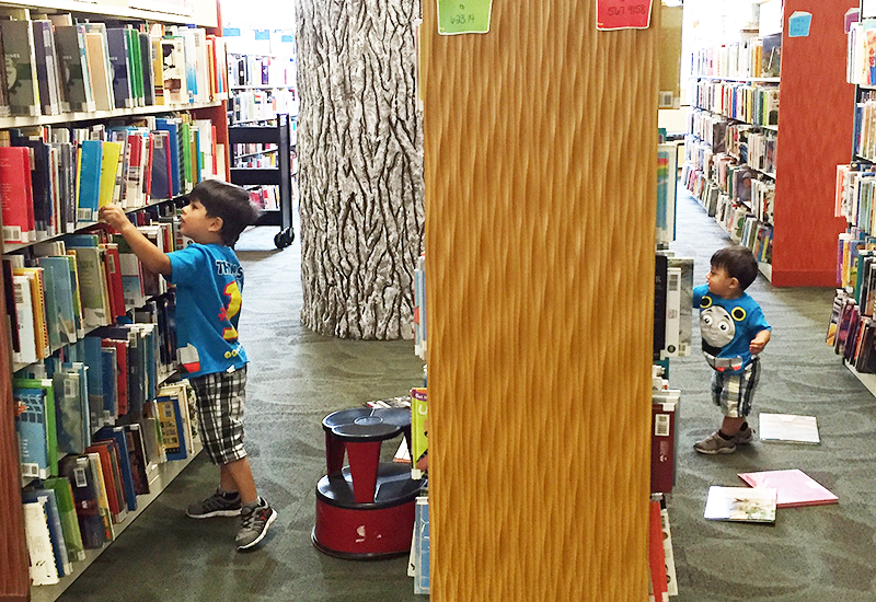 Two kids looking through book stacks in the Children's Room, 2016
