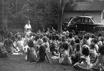 Elinor Haff reads to youngsters on back lawn, 1949